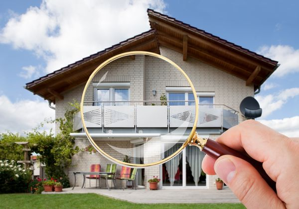 inspecting house with magnifying glass